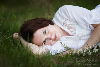 Romantic young woman portrait in Riga laying on grass