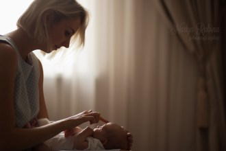 Мама нежно гладит малыша во время домашней фотосессии