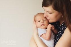 Мама обнимает малыша во время домашней фотосессии.