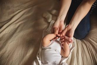 Мама держит ножки своего малыша во время домашней фотосессии.