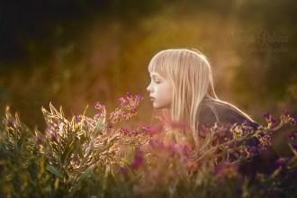 Портрет девочки на природе среди трав и цветов.