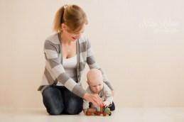 Мама и полугодовас-сыночек играют с паравозиком в фотостудии.