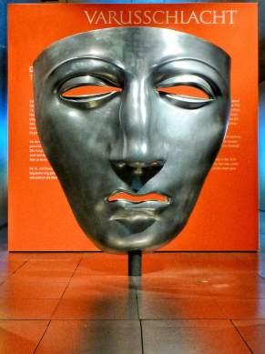 Symbol der Varus-Schlacht. Stark vergrößerte Darstellung der eisernen Gesichtsmaske eines Reiterhelms, die in Kalkriese gefunden wurde.