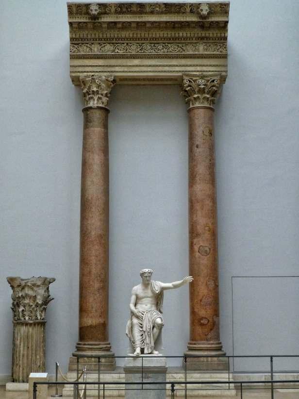 Statue eines römischen Kaisers mit dem Kopf von Trajan vor zwei Säulen des Jupiterheiligtums aus den Tempelanlagen von Baalbek. Ausgestellt im Berliner Pergamonmuseum.