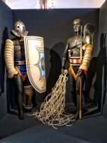 Der Retiarius (rechts). Mit Wurfnetz, Dreizack und Dolch bewaffnet, trat er überwiegend gegen den Secutor an. Der Secutor (Verfolger) ist besser geschützt, doch sein Helm schränkt sein Blickfeld ein und seine Defensivwaffen machen ihn unbeweglicher.