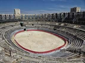 """Die Fassade ist 21 m hoch und besteht aus zwei Reihen von Arkaden. Gegen Ende des 6. Jahrhunderts wurde das Amphitheater zu einem befestigten Siedlungskern mit etwa 200 Häusern umgenutzt. Aus dieser Zeit stammen auch die beiden hier sichtbaren von insgesamt vier Wehrtürmen. Heute wird die """"Arena"""" für unblutige Stierkämpfe und für Konzerte genutzt."""