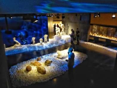 """Farben und Licht, Geräusche und Animationen bilden den atmosphärischen Rahmen der Ausstellung """"Das Schiffswrack von Antikythera"""" im Antikenmuseum Basel."""