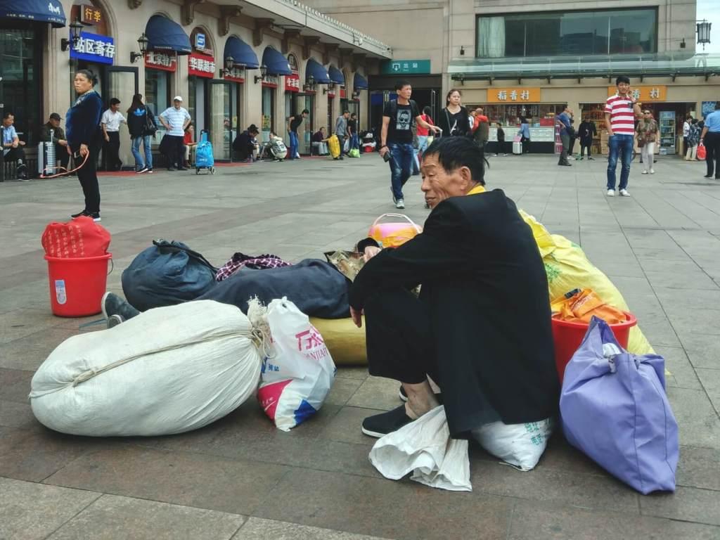 Pasażerowie czekający na pociąg na dworcu w Pekinie.
