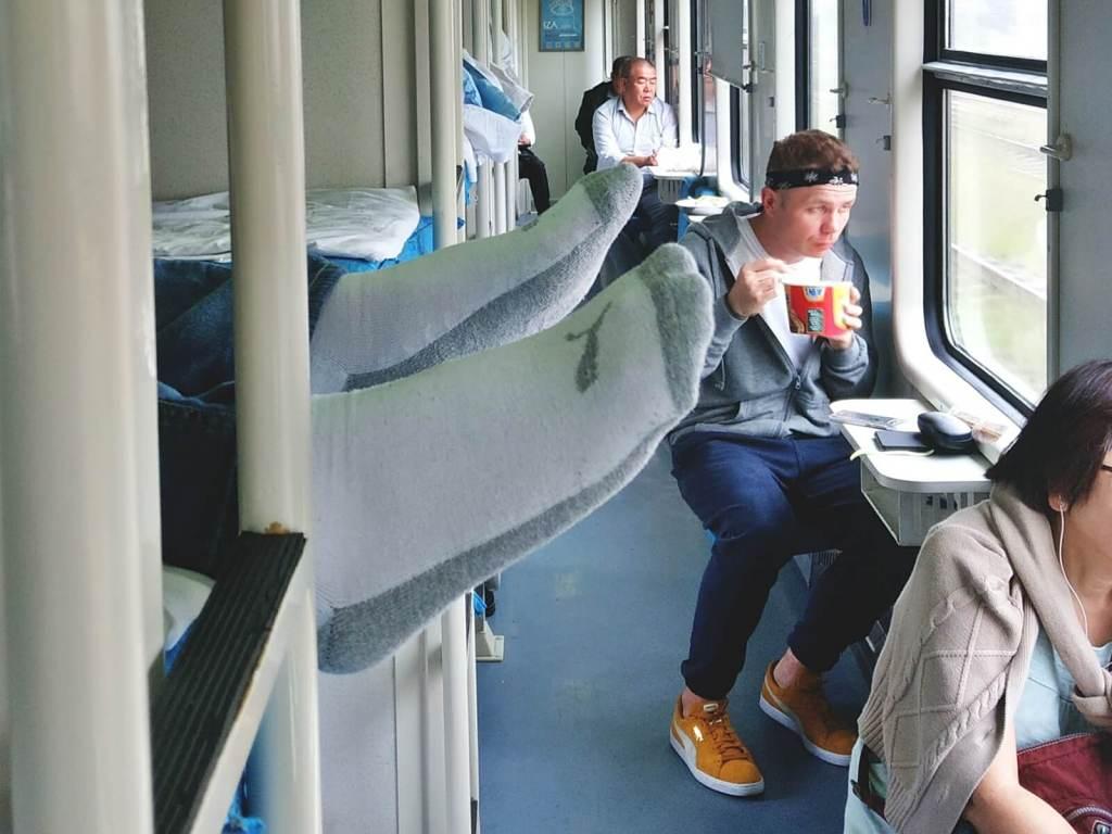 Bloger podróżniczy je nudele w chińskim pociągu.
