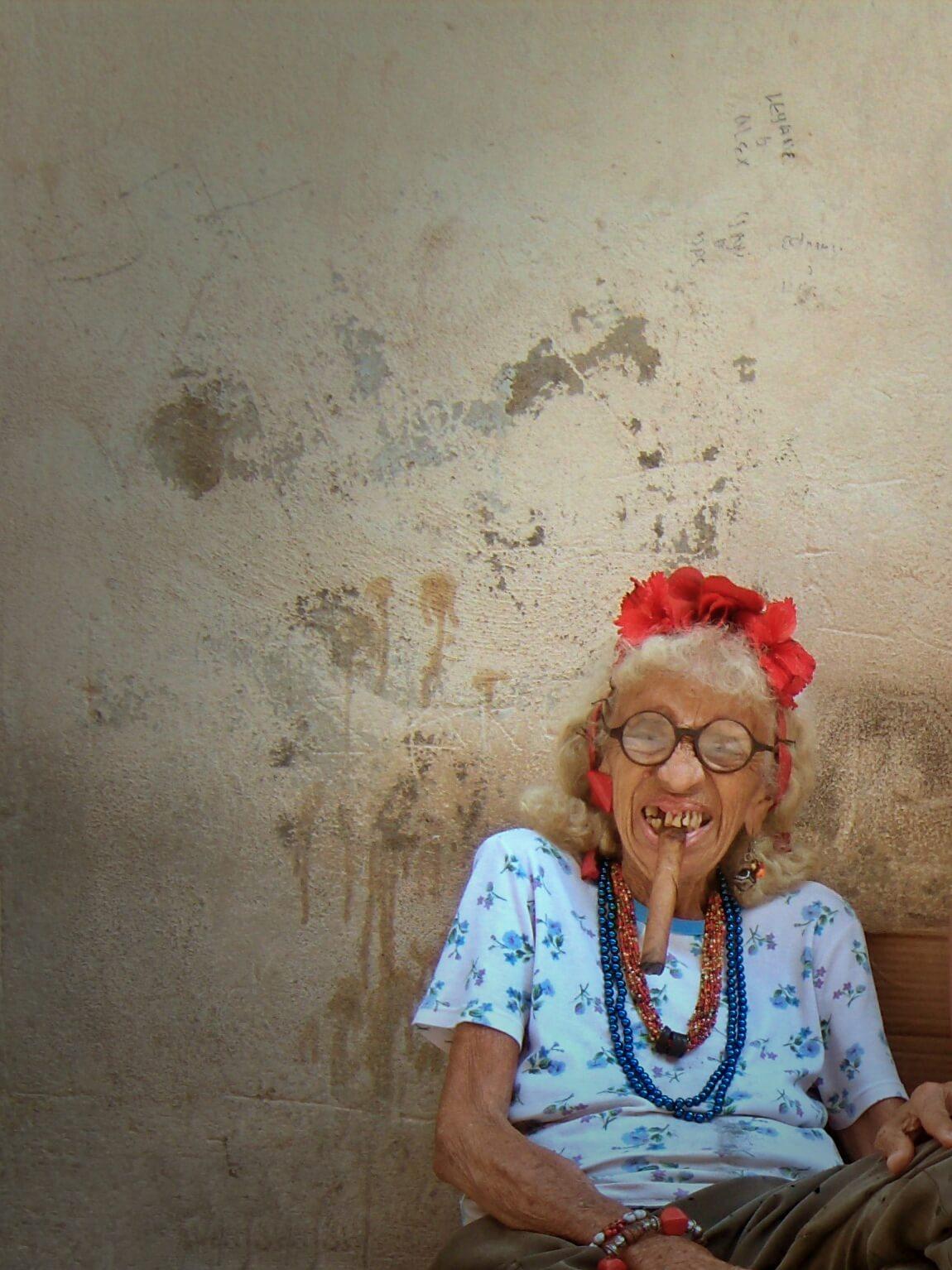 Stara Kubanka w okularach paląca cygaro.