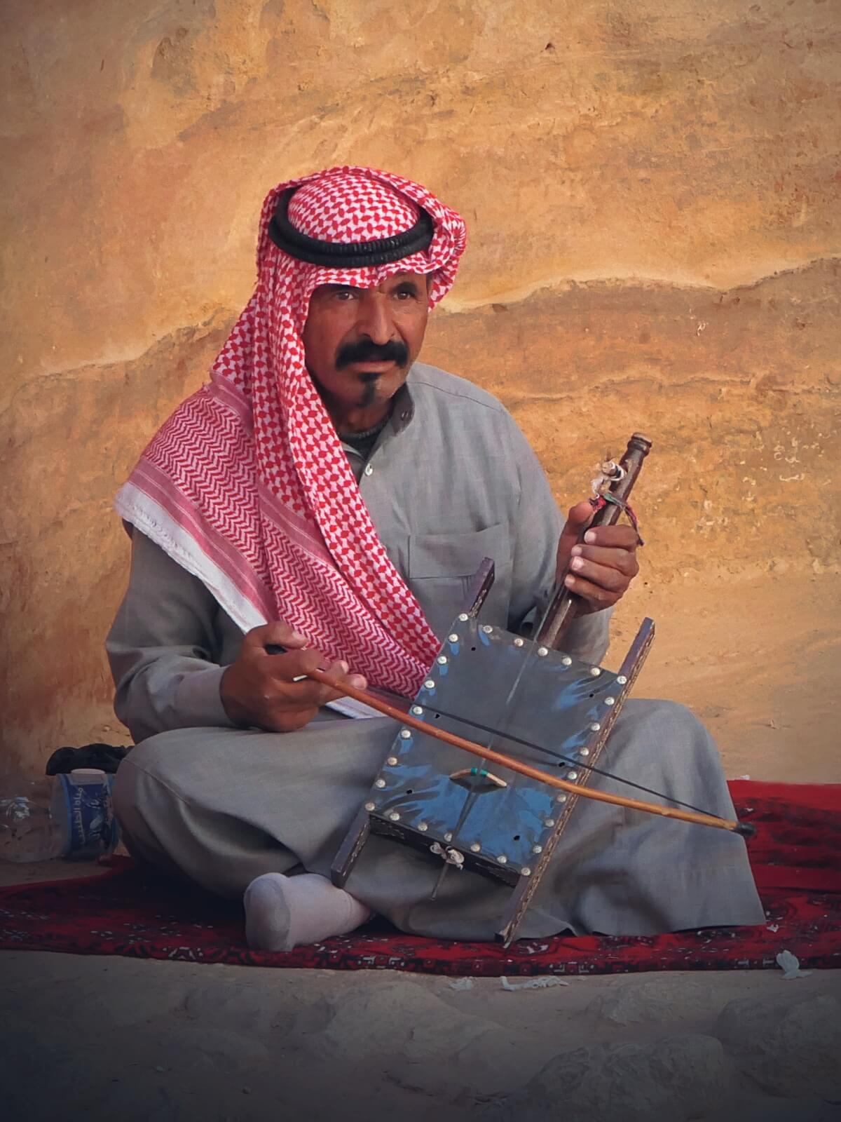 Beduin gra na tradycyjnym instrumencie na pustyni w Jordanii.
