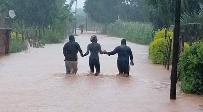 Three people walk through light flooding in Limpopo due to storm Eloise.