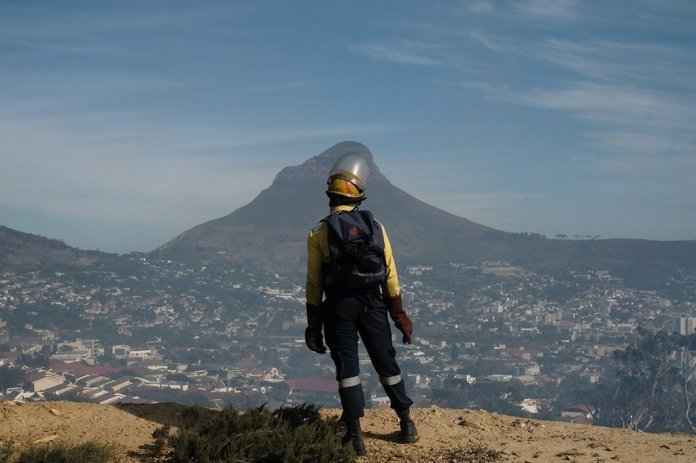 A firefighter looks out across the city as rescue