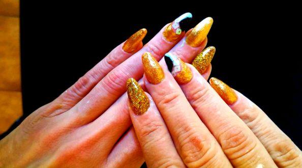 Nail art design con colore oro, decorazione astratta con nero e paillettes olografici
