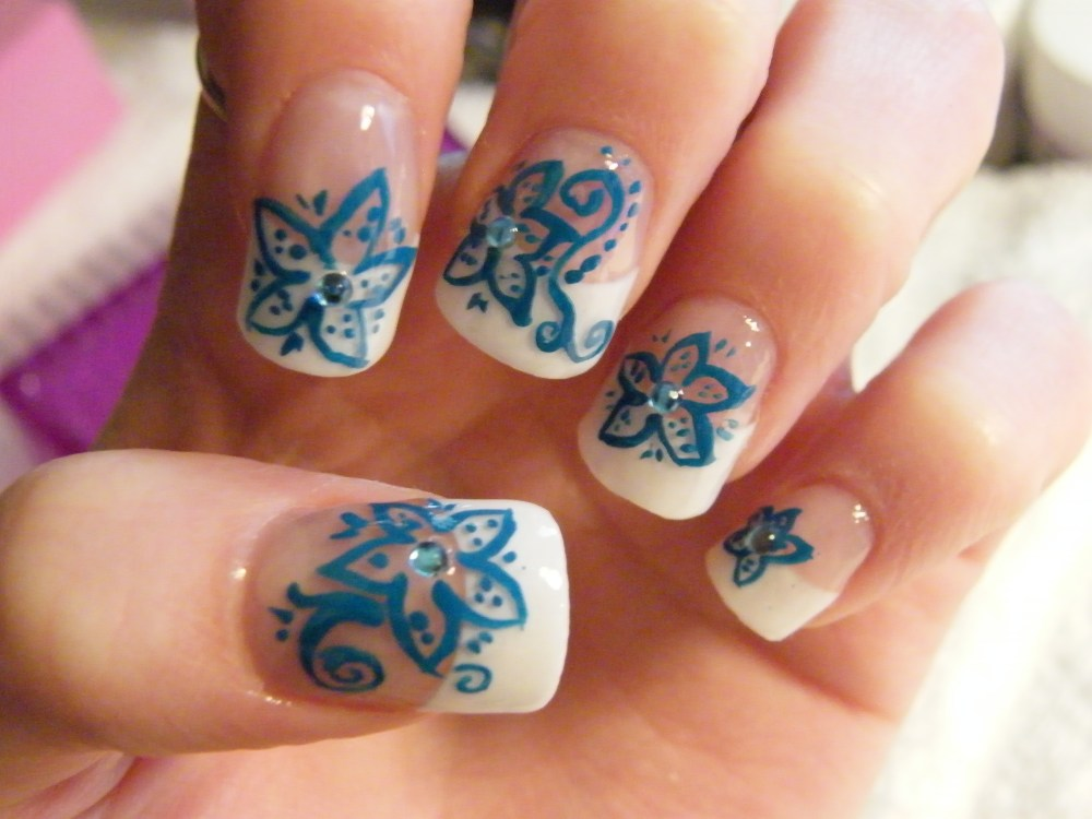Acrylic nails with handpainted blue flowers and rhinestone