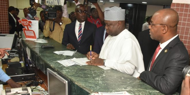 Lagos State Governor Mr. Akinwunmi Ambode (2nd right), filling his Land Use Charge payment form at Guaranty Trust Bank, Opebi, Ikeja, on Monday, February 19, 2018. With him: Special Adviser on Revenue and Tax, Mr. Fola Lasisi (right)