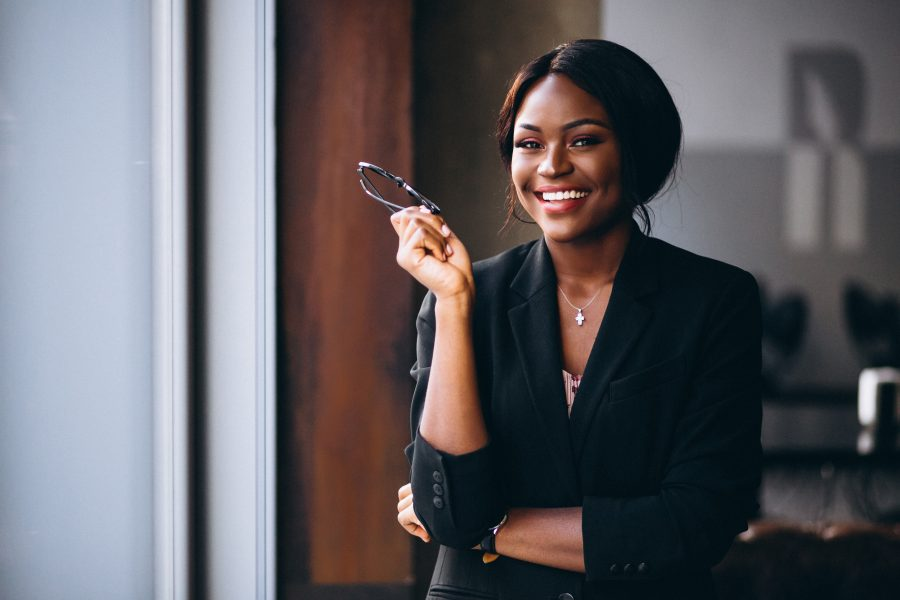 5 Financial tips for women in 2021, Lifestyle Inflation, African american business woman by the window, Things to accomplish during COVID-19 lockdown