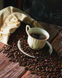 cup of black coffee on top of coffee beans and saucer