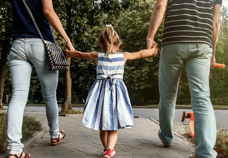 mon and dad holding hands with little girl namaste family services