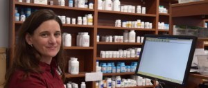 A pharmacist stands in front of a computer, smiling at camera. In the background are medications.
