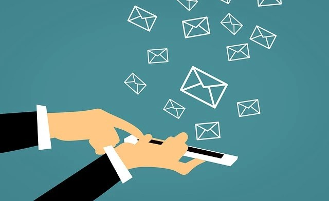 hands holding mobile phone sending emails