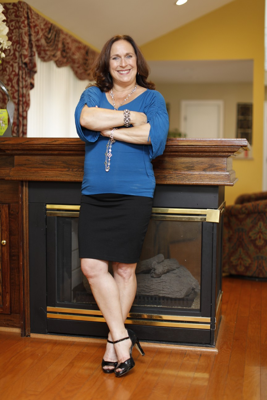 Business coach Nancy Ganzekaufer at home by the fireplace