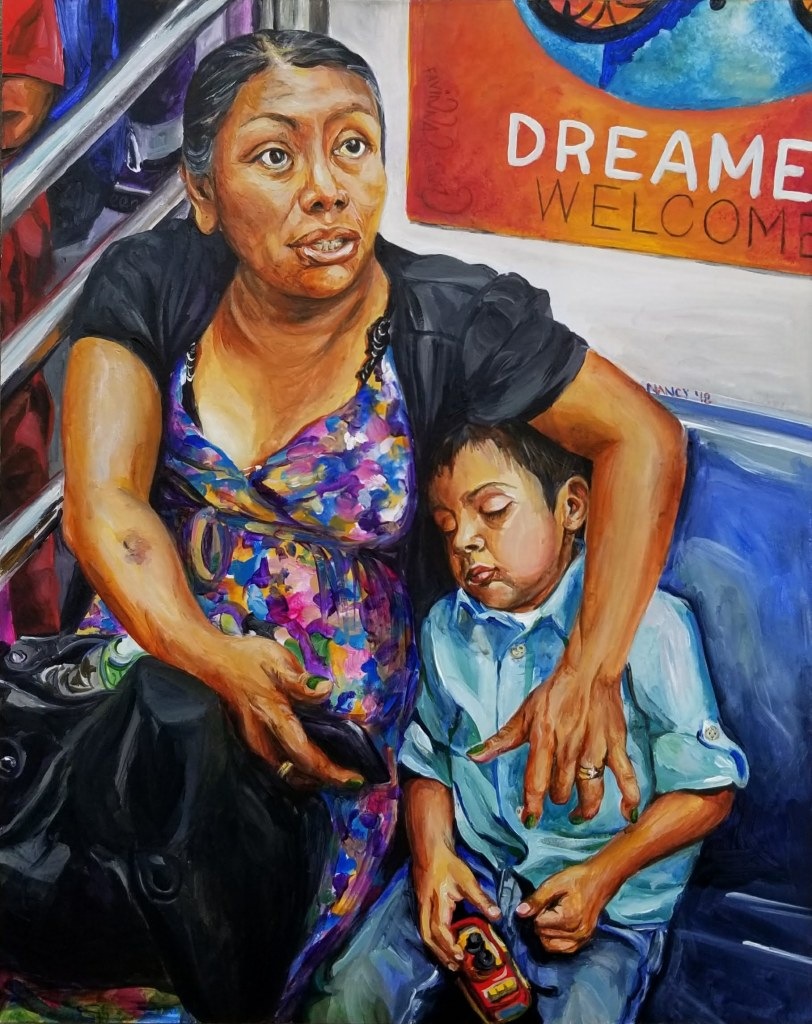 "A Latina Mother holds her young son (3 yrs old) on a subway in NY City with a poster entitled ""Dreamers Welcome"" behind her."