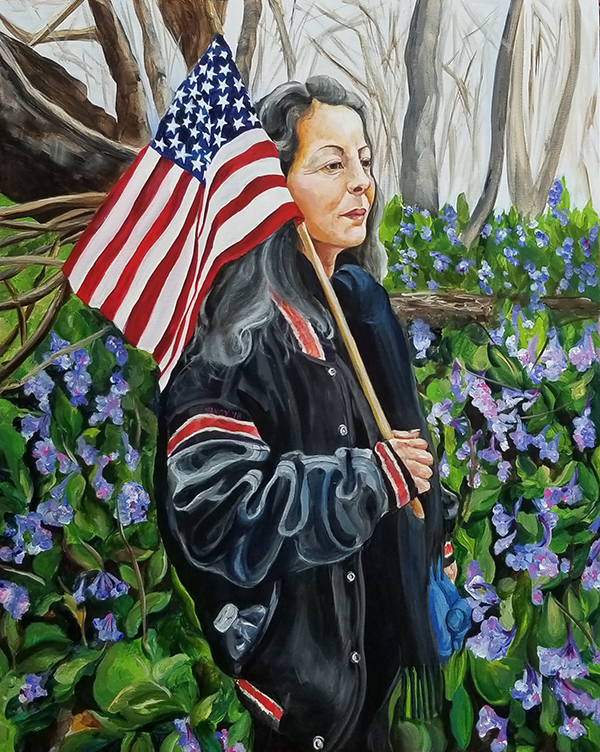 A petite woman in a black jacket, salt & pepper hair, holding an American flag stands in a field of Virginia Bluebells.