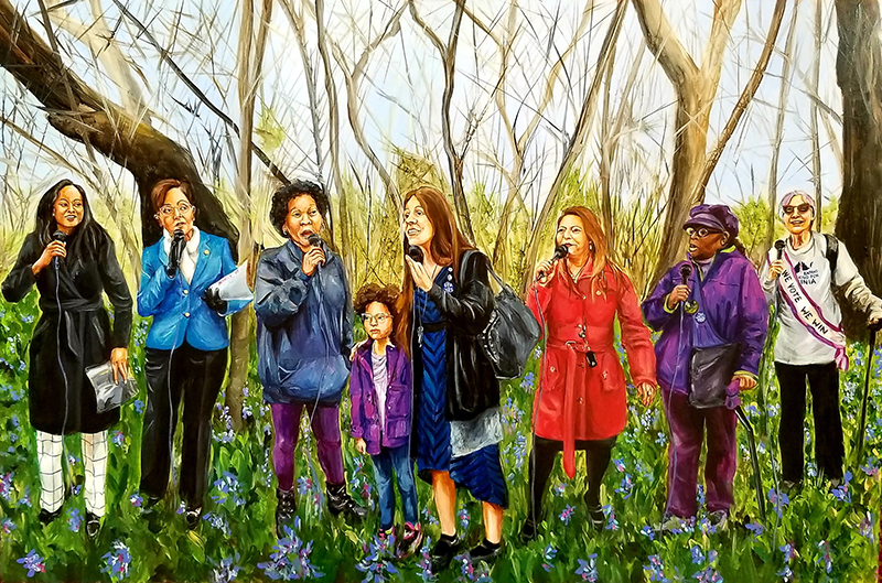 A row of 8 women standing in a field of wild bluebells near the Shenandoah River, each holding microphones taking turns to talk. Jennifer Caroll Foy, Hala Ayala, Danica Roem, Elizabeth Guzman, Marilyn Karp.