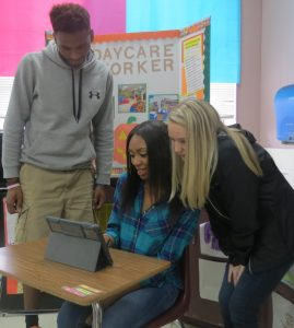Reggie McWilliams, Deja Hasan, and Elizabeth Holland look over the final video that the class produced for daycares.