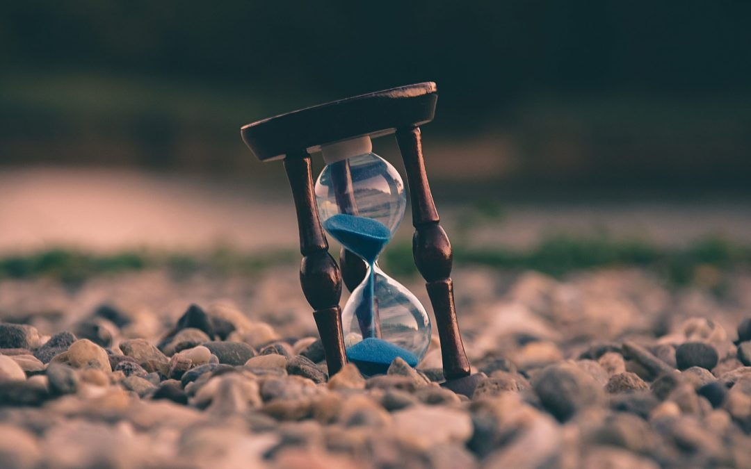 An hourglass on vacation in the beach sand