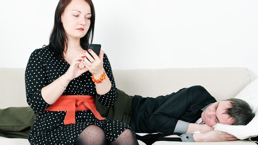 Жена проверяет телефон своего спящего мужа
