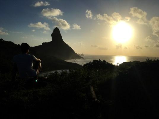 Rodrigo de costas no alto do Forte de Nossa Senhora dos Remédios aguardando o sol se por.