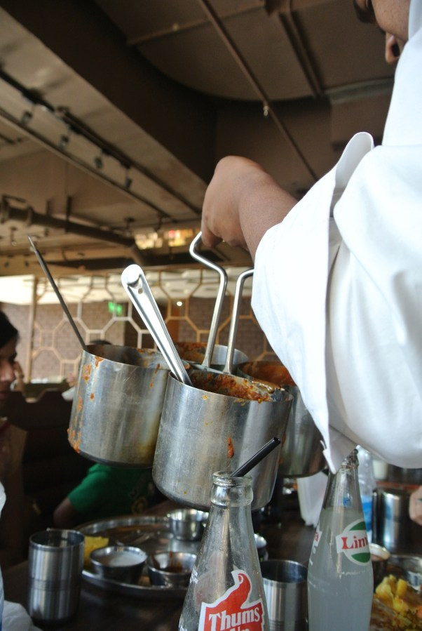 Server scooping curries and dishes into the thalis.