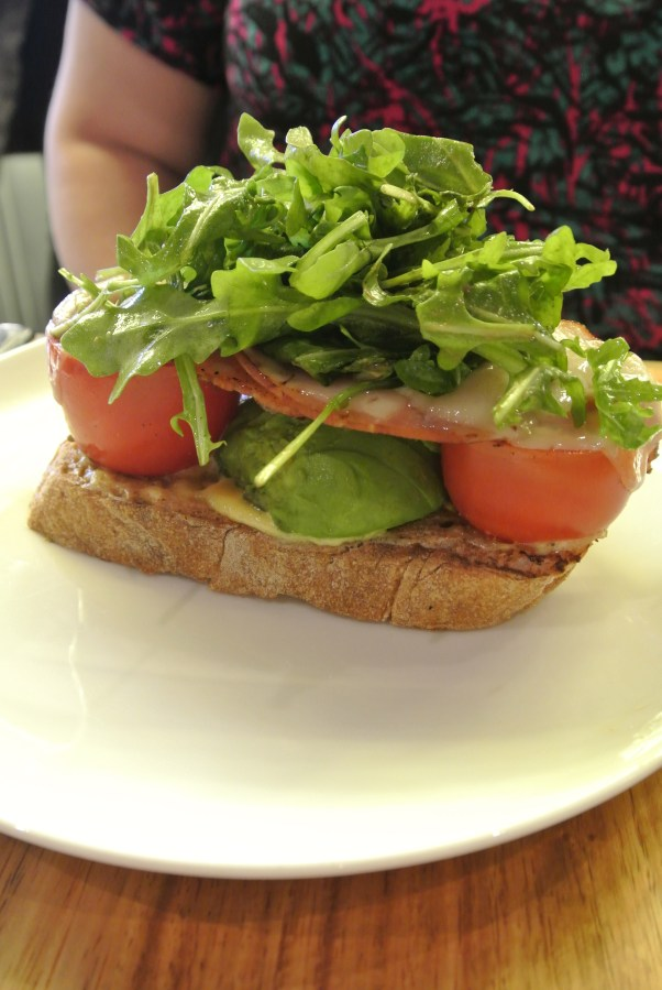 The Breakfast BLT - bacon, cheese on tomato, avocado and garlic toast topped with a bunch of rocket.
