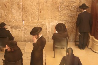 Orthodox men praying at the Western Wall's underground tunnels.
