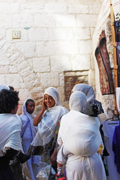 Pilgrims at the Fifth Station of the Cross on Via Dolorosa. People from all over the world come to touch this ancient stone said to carry the handprint of Jesus.