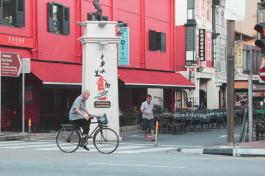 man riding his bicycle through Chinatown