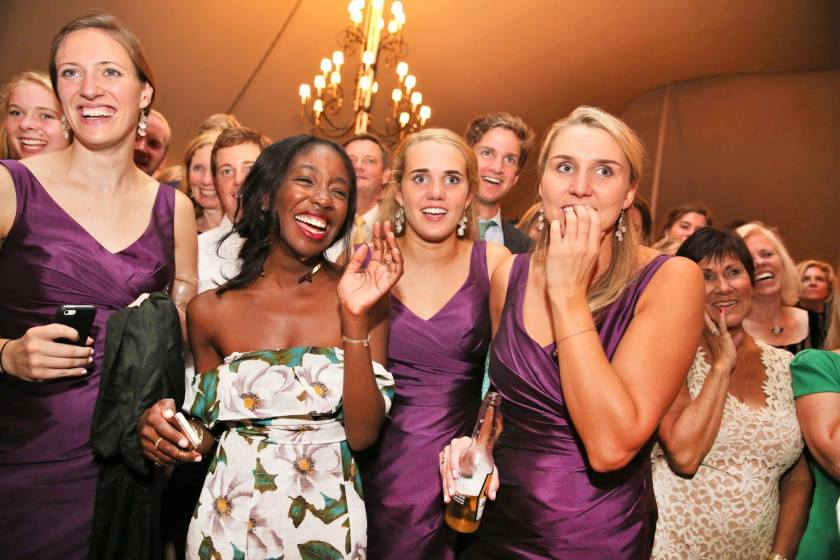 Me laughing at a wedding with bridesmaids surrounding