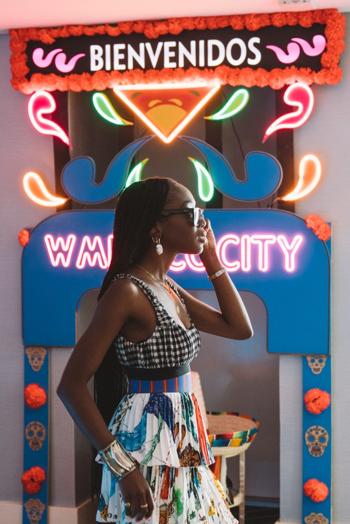neon sign saying W Mexico City and girl standing in front of it