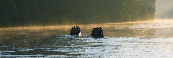 Przeprawa na łódeczkach w świetle wschodzącego słońca.