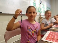 Maggie shows the keychain that she made. Each bead represents someone in her family. Grace is behind her
