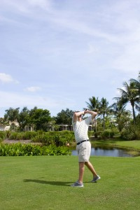 Male golfer taking a swing on a Florida golf course