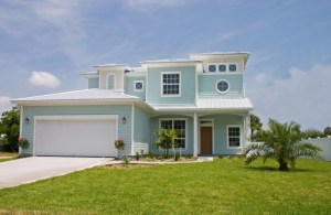 Contemporary two story home, light green siding, palm tree in the yard
