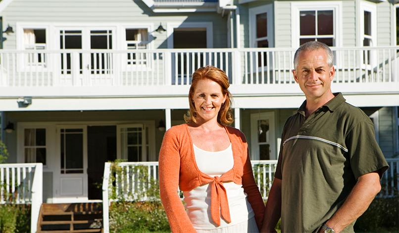man and woman in front of two story house