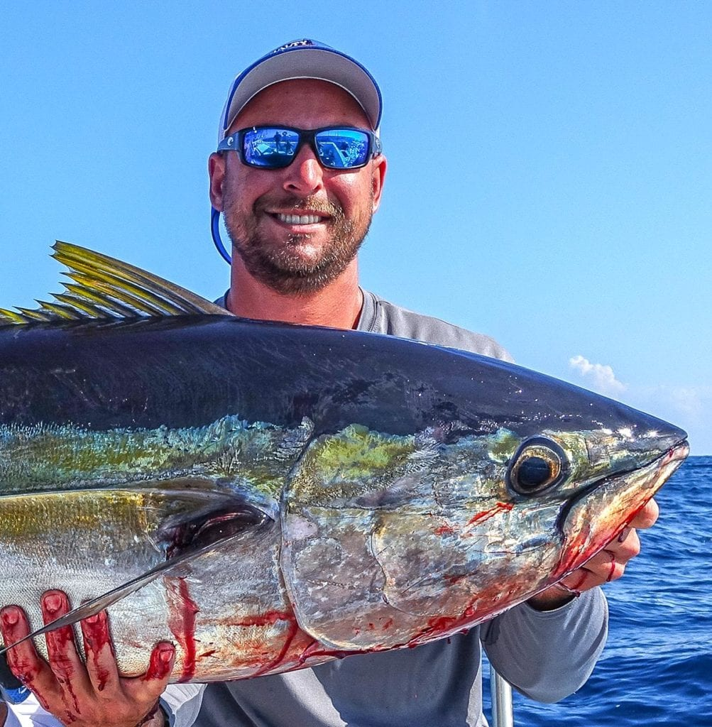 The captain at Naples Fishing Boat holding a yellowfin tuna he caught on a private fishing trip