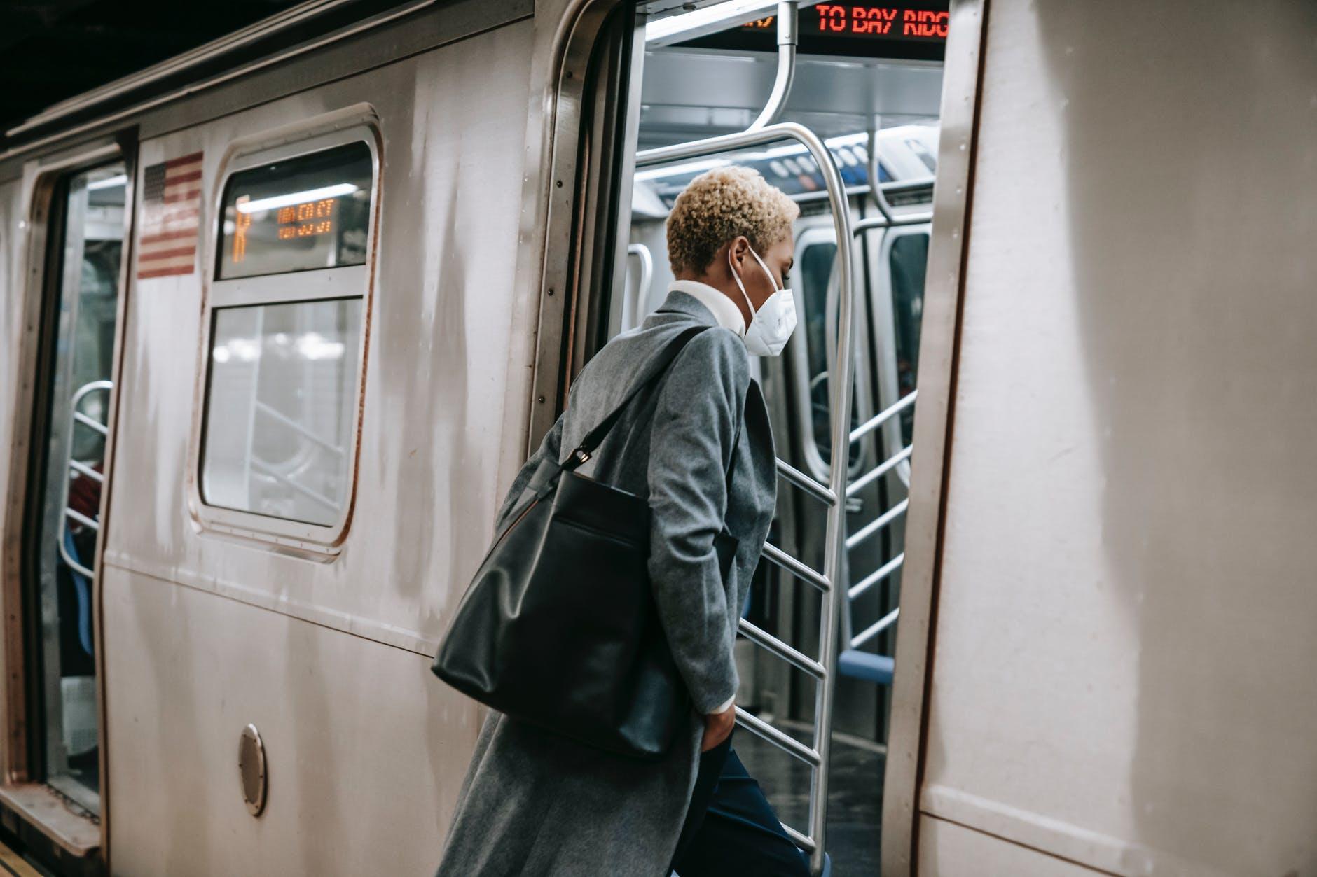 black woman in mask entering metro train