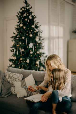 girl sitting on woman s lap while holding pen and paper, kerst in de narcistische familie