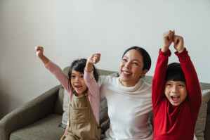 happy asian woman with kids cheering while watching tv, onoverwinnelijk worden