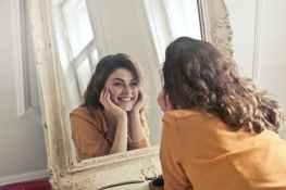 photo of woman looking at the mirror, gevoel van eigenwaarde vermeerderen